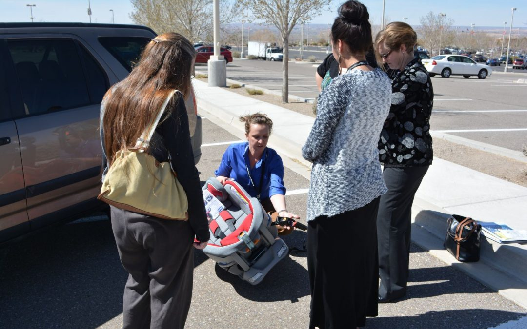 technician teaches parents how to install car seats